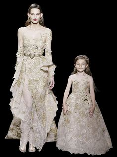 Long dress in lace and guipure, round collar neckline and long sleeves, asymetric basque, foliage and birds embroidered with anthic gold silk threads, sequins, crystal stones and silk organza flowers.