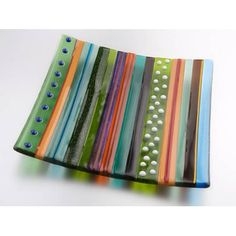Inspired by the breadth of colour in the Hockney paintings this piece of handmade kiln-formed glass explores texture and colour in a linear pattern reflecting motifs found in the paintings of the Yorkshire woods. This exclusive design is individually handmade in the UK by the designer Janette Garthwaite and therefore each piece is unique. The dish measures 18cm square