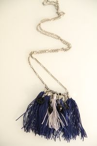 A unique tassels necklace with blue and silver tassels , black charms, and silver chain.