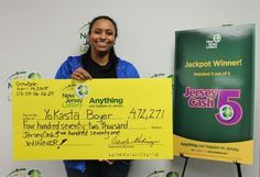 Some people have all the luck ... and tax bills associated with big lottery winnings. PHOTO: YoKasta Boyer holds her winning New Jersey Lottery big check.