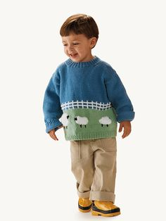 Children will love feeling the soft fluffy black-face sheep on this rural landscape sweater.