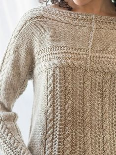 A simple cable motif is framed by eyelets to create the top half of Zinaida. The yoke is knit from the sleeve cuffs to the middle of the body, then the pieces are joined with a three-needle bind off. Stitches are picked up and knit down to form the rest of the body, making this an easy sweater.