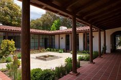 The firm extended the house back, adding a wing with a covered walkway on either side. The architects had to excavate and remove two floors to get to the original terracotta flooring, restoring it with custom 10-inch-square Terra Bella tiles from Mission Tile West.