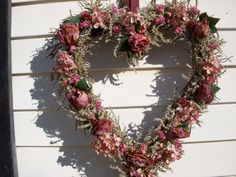 Heart made from birch twigs in Victorian style and decorated with dried roses and flowers