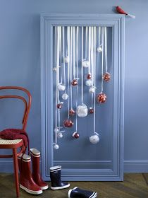 Attach Christmas ornaments to ribbon and hang them inside a picture frame.