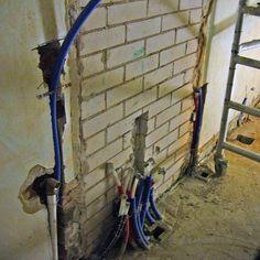 4/15 Valun jälkeen uuteen kylpyhuoneen runkoon alettiin tuomaan uusia talotekniikkavetoja. Nämä roilottiin suojaputkissa tiilirungon sisään. Tässä on vasemmalta katsoen pesukoneen viemäri ja tulovesi sekä siitä seuraavana koko asunnon käyttövesien jakotukki.