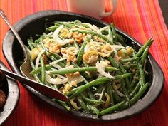 Tender-crisp green beans tossed in a savory dressing flavored with anchovies and Worcestershire. Hot and tangy pepperoncini, shallots, and pinenuts finish the salad.