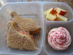 Dinosaur salami-and-cheese sandwiches, apples and a homemade cupcake.