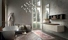 Morgenmantel an der Wand aufhängen, Tisch für Badewanne mit ein Haufen Tücher, kliner marokkanischer Teppich, Wand mit Mustretapete, Designer Kronleuchter aus Glas, Tür zum Gartenbereich