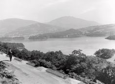 Postman on mountain road near Derwent Water. Postman in foreground, and a panorama of Derwent water and surrounding hills in the background. Royal Mail, Post Office, Vintage Photos, Archive, Mountain, River, Photographs, Outdoor, Outdoors