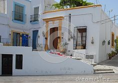 Photo made in Nijar in Andalusia (Spain). In the picture you can see the facades of two houses, one behind the other, characteristics of the country and Andalusia. The white walls are brightened by the colors of frames, vases for flowers and the dark of the doors and windows.