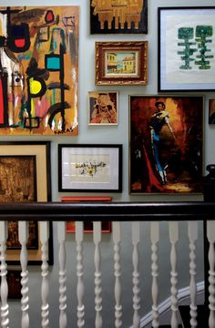 blue walls paint color and eclectic art gallery with black banister and white spindles.