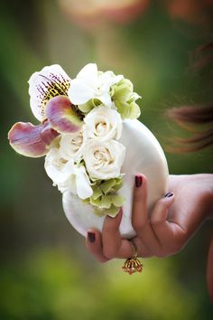 Unique bouquet idea: tucking flowers in a pearlescent nautilus shell.  This may be too unique but it's inspiration. Maybe use some starfish too or something
