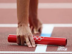 An athlete holds the baton during the Women's 4 x 400m Relay Round 1 heats on Day 14.