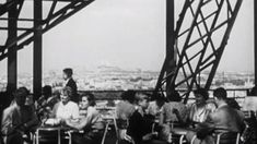 Tourists visit and dine at the Eiffel Tower in Paris back in the 1950s while a violinist serenades them.