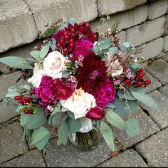 Berry colored bridal bouquet with burgundy dahlia and hypericum, blush roses, pink stock, chocolate lace flowers, pink and white ranunculus and assorted eucalyptus.