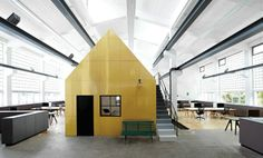 Designliga's cavernous Munich workspace has a pair of two-storey house-like structures within it - one gold and one white - used as work and meeting space