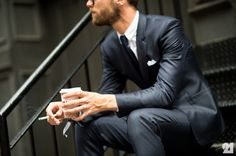 Man with tattooed hands in suit