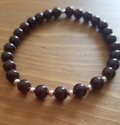 This beautiful beaded bracelet has been made using garnet beads, 3mm sterling silver beads and strong elastic thread.Garnet is thought to reduce toxins and regenerate the body and can stimulate the metabolism. It has protective and calming properties and it's helpful when healing the emotions. When placed under the pillow garnet can help reduce bad dreams and is a useful to have during a crisis. Lucky for love, success and achieving your goals. Relates to the base and hear...