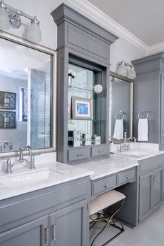 Storage between sinks, framed out mirrors, gray cabinets...