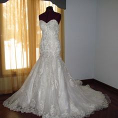 Breathtaking lace trumpet wedding gown embellished with delicate flowers that enhance a sweet heart neckline. Beautiful flower lace graces the bodice of this wedding gown that cascades into a drop waist that is embellished with crystals, beads and pearls to a flowing lace appliqued chapel length train.
