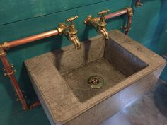 Handmade concrete sink with exposed copper piping and brass bib taps. www.arnoldskitchens.co.uk