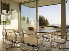 Located on the bluffs overlooking the Pacific Ocean, the sqf Zeidler Residence, designed by Ehrlich Architects, arranges interior and exterior. Glass Pocket Doors, Sliding Glass Door, Elegant Dining Room, Dining Room Design, Dining Rooms, Dining Area, Kitchen Design, Dining Table, Stainless Steel Staircase