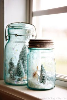Glue clear marbles on the bottom of the items to raise them off the bottom of jar or lid (depending on if right side up or upside down) then add enough fake snow to cover marble.  Bluish glass would be perfect. LA SOURCE