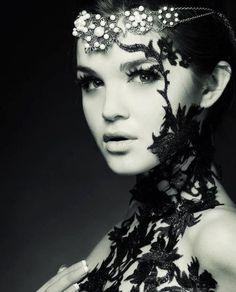Headpiece & black lace climbing her face. Very avant garde.