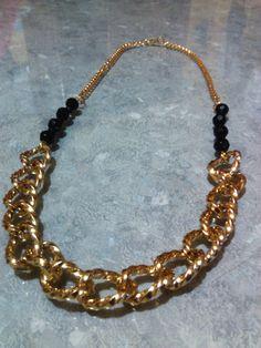 Collar de cadena en color oro. con detalle de piedras negras.