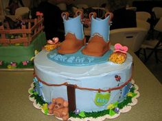 Little boy's baby shower cake with 50/50 fondant/gum paste boots, butterflies, hay bales, teddy bear, and clothes. Whipped icing with buttercream decorations.