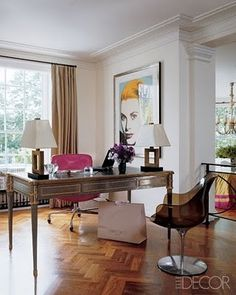 An ecclectic feminine office featured in Elle Decor with parquet timber floors, a traditional desk, hot pink upholstered desk chair and modern pop art