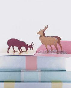 Create a pop-up card featuring a pair of reindeer with little fairy-tale touches, including a patch of glitter that mimics the wintry forest floor.