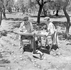 General Sir Bernard Montgomery (left), Commander-in-Chief of the British Eighth Army, and General G. G. Simonds, General Officer Commanding of the 1st Canadian Infantry Division, consulting maps at the 1st Canadian Infantry Division Headquarters near Valguarnera, Italy, July 20, 1943