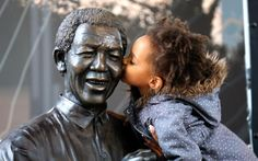 Malika is lifted by her mother to kiss a statue of former South African President Nelson Mandela before a service conducted by Archbishop Desmond Tutu at the Nelson Mandela Foundation in Johannesburg, South Africa. South African Girl Names, Nelson Mandela Death, 6 Word Memoirs, Nelson Mandela Foundation, African Words, Desmond Tutu, Black History Books, Order Of Service, Vintage Classics