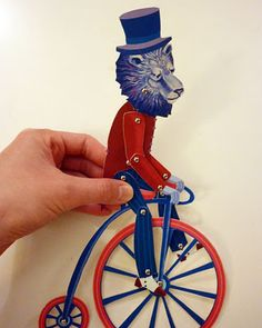 Paper lion, on a paper penny farthing.