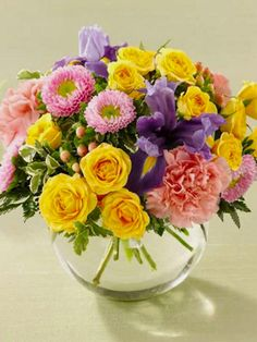 Leticia: Arreglo primaveral de minirosas, iris, maules acompañadas de hypericum en florero de vidrio.