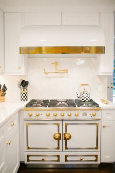 Peppermint Bliss - Kitchen features white barrel range hood suspended over antique brass pot filler paired with La Cornue Cornuefe Stove in White with Brass Finish.