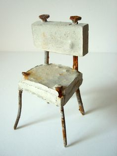 miniature chair made from rusted nails and concrete