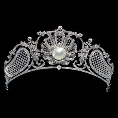 An Edwardian platinum, diamond and pearl tiara, British or French, circa 1907. The tiara with lattice, lace and foliate motifs, centring a bouton pearl measuring 1.4cm diameter, and set throughout with diamonds, the edges of the tiara frame millegrain set with diamonds, mounted in platinum. The central shell motif could be worn separately as a brooch but the fittings have been lost. #Edwardian #BelleEpoque #tiara