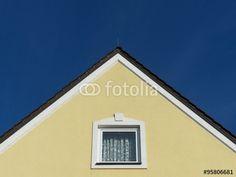 Kleine Dachwohnung mit Fenster und Gardine in einer gelben Fassade mit spitzem Giebel in Bayern