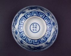 Large porcelain bowl. Underglaze blue with wide band of two five-clawed dragons chasing flaming pearls among clouds. Stylised cloud form in a double circle inside, with classic scrolls around the rim. Inscription on base.