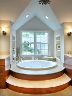 circular bathtub, vaulted ceiling, large window.