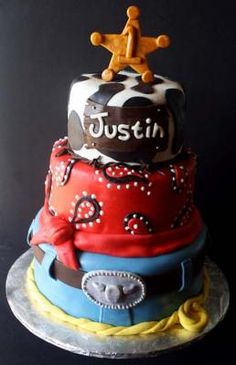 A Cowboy Theme Birthday Cake  This cake is perfect for the little aspiring cowboy in your life. Topped with a badge and bandana details around the cake, this cake definitely fits the bill for being western.