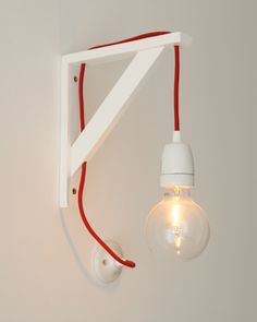 DIY wall light made with red tissue wire, ceramic socket and wooden angle bracket
