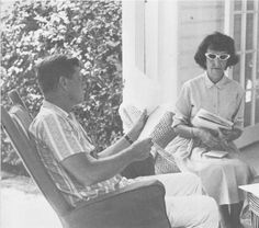 JFK looks over some paperwork with his secretary, Evelyn Lincoln nearby.