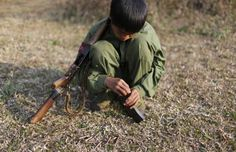 A 15-year-old rebel soldier of the Myanmar National Democratic Alliance Army inserts bullets into the clip of his rifle near a military base in the Kokang region on March 11. (Reuters)