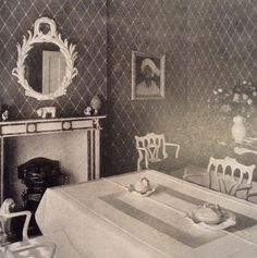 Syrie Maugham's own Park Lane dining room, with green and white medallion wallpaper, a Serge Roche console and Chinese Chippendale inspired dining chairs. c1940's