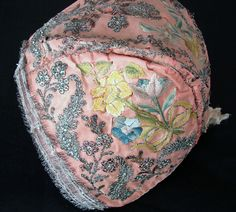 18th C. Silk Embroidery Child's Bonnet w/ Flowers and fine silk embroidered floral bouquets tied with ribbons. There are ornate meandering leaves and flowers worked in metallic threads and tiny sequins with a wider metallic fringe border around the edge.