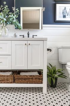 A+white+dual+washstand+sits+on+black+and+white+hex+floor+tiles+in+a+white+and+navy+blue+cottage+bathroom.